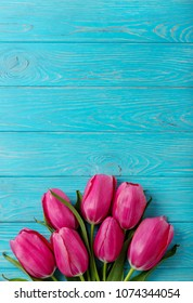 Bouquet of pink tulips on a blue wooden background. View from above. Selective focus.