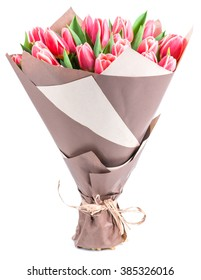 bouquet of pink tulips in a package of kraft paper, isolated on white background, shallow DOF