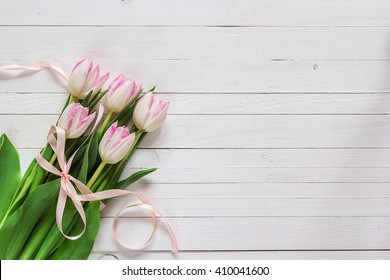 Bouquet of pink tulips with pink ribbon on white painted wooden background and empty space for text. Top view with copy space