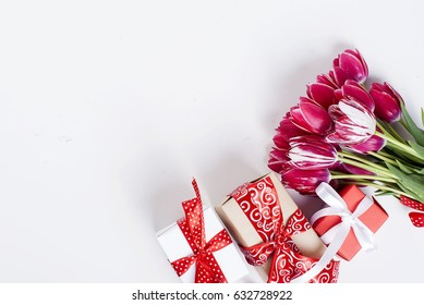 A bouquet of pink tulips in a vase and gift box with red ribbon on a white table, top view. Copy space.