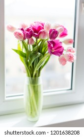 A bouquet of pink tulips in a vase on window sill. Soft selective focus.