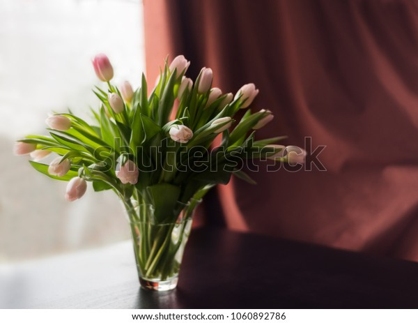 Bouquet of pink tulips in vase on the table, window and brown curtain as a  background