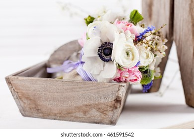 Bouquet from pink tulips, violet grape hyacinths, white anemones, violet veronica and white buttercup with violet ribbon lying in the old wooden basket with white background