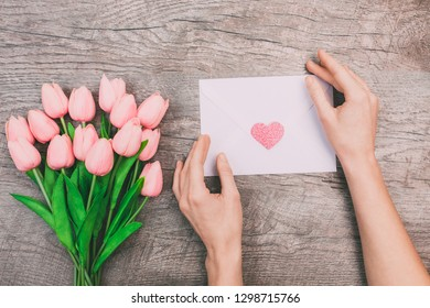 A bouquet of pink tulips and women's hands are holding a blank envelope with a heart, on a wooden background. Valentine's Day