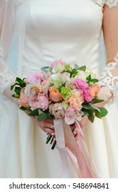 Bouquet of pink and white peonies held by bride in lace dress