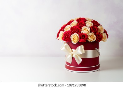 A bouquet of pink and white roses decorated in a hat box on a light background.