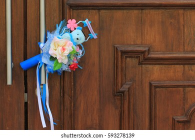 bouquet of plastic flowers and teddy bear for congratulating on the wood door handle