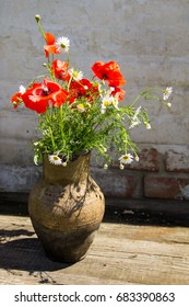 Bouquet of poppies and daisies in clay jug on rustic wooden table against old brick wall