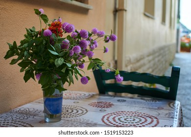 Bouquet of purple flowers  in vase on table - taken in side street in Greece