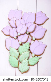 Bouquet from purple gingerbread cookies in the shape tulips on wooden table