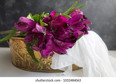 A bouquet of purple lilies in a brass tin with a silky white cloth.  The botanical name is Alstroemeria, but commonly known as Lily of the Incas or Peruvian Lilies.
