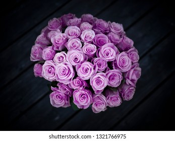 Bouquet of purple roses on dark wooden background