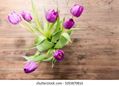 Bouquet of purple tulips on a wooden table