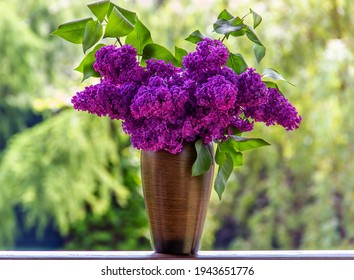 Bouquet purple (Violet) Lilac Flower  in a brown vase. Syringa vulgaris (common lilac). Spring flowers.