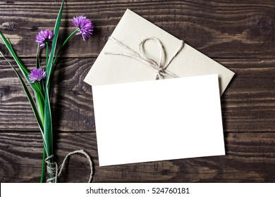 bouquet of purple wildflowers and blank white greeting card with envelope on brown rustic wood background for creative work design. flat lay