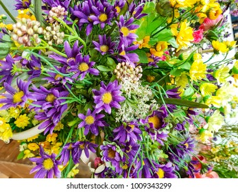 Bouquet of purple and yellow.Placed in a wooden crate.In a flower shop