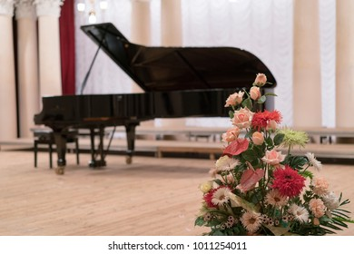A bouquet of real flowers on the background of a black grand piano that stands on the stage