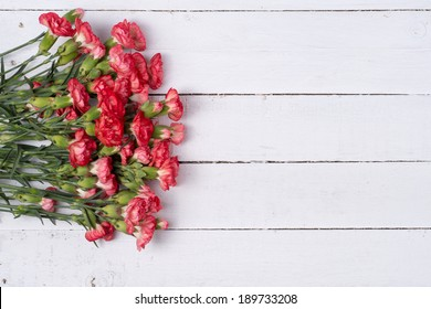 Bouquet of red carnation flowers on wooden background. Top view, copy space