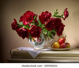bouquet from red peonies in ceramic vase with plate of apples and pear on table on beige background