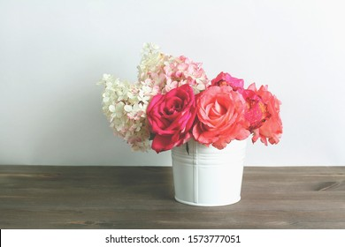 bouquet of red, pink roses and hydrangea flowers in white bucket on dark wooden table. retro filter.