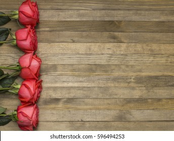 bouquet red pose flowers and  paper notebook wooden background