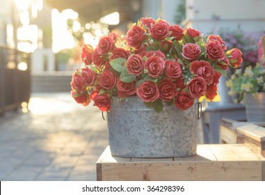 Bouquet of red roses in bucket on wooden crate, filtered image