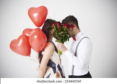 Bouquet of red roses covering couple kiss