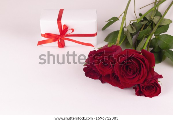 A bouquet of red roses and a gift with a ribbon lie on a white background.