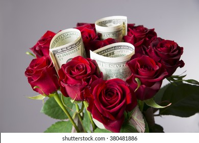 Bouquet of red roses with a hundred-dollar bills on a gray background. Present at the International Women's Day