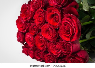 Bouquet of red roses laid on a white surface.