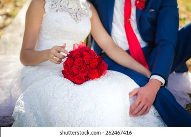 bouquet of red roses on the bride's knees