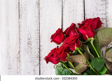 c3bc6b3d586c1b Bouquet of red roses on a light wooden background. Top view