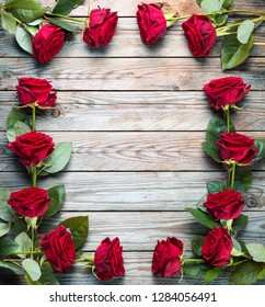 Bouquet of red roses on wooden rustic background.