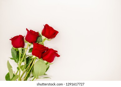 Bouquet of red  roses with a red ribbon. Eights march woman's day, holiday. Flowers on a white background copyspace. Horizontal top view