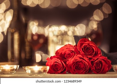 Bouquet of red roses in a romantic restaurant setting.