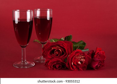 bouquet of red roses and two glasses of wine on a red background