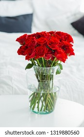 A bouquet of red roses in a vase on a table in a bright room. Luxury bouquet in gift woman.