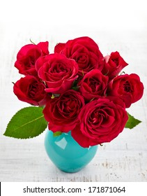 Bouquet of red roses in a vase on white wooden background