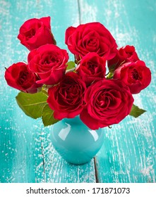 Bouquet of red roses in a vase on blue wooden background