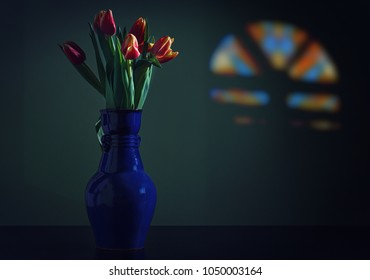 Bouquet of red tulips in a blue vase on a dark background.