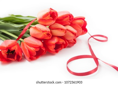 Bouquet of red tulips isolated and lied on white background close up. With red ribbon