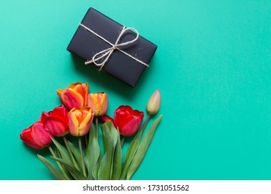 Bouquet of red tulips with present wrapped in black paper with packthread on green background. Photo with copy blank space.