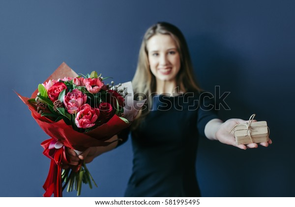Bouquet of red tulips and surprise woodenbox in girl's hands.