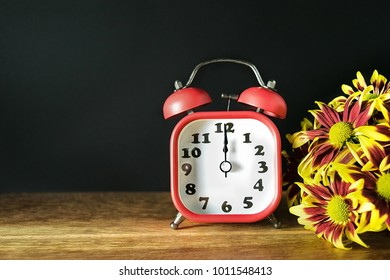 A bouquet of red and yellow flower on old wood, the background is black. still life flower.