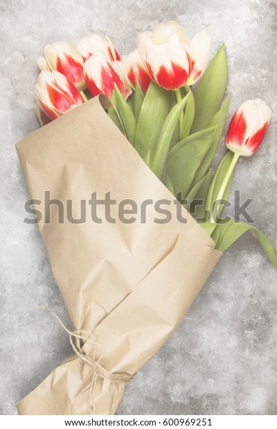 Bouquet of red-white tulips in kraft paper on a light background. Top view. Toning.