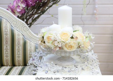 a bouquet of roses and candles in the white pot