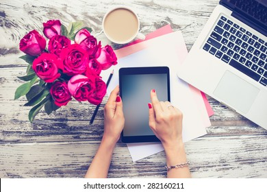 Bouquet of roses, cup of coffee, female hands with tablet and laptop on old wooden table. Top view. Toned image