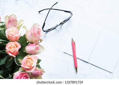 Bouquet of roses with glasses and notebook