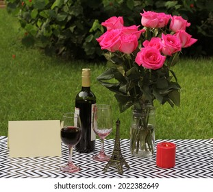 Bouquet of Roses on Outdoor Table With Wine and Candle