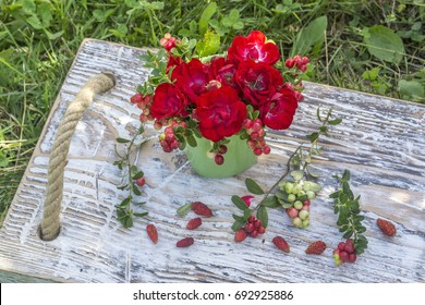 Bouquet of roses on a wooden tray.